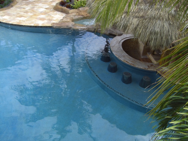 Faux rock pool bar in the pool by Sammet Pools - South Florida Pool Designer and Builder